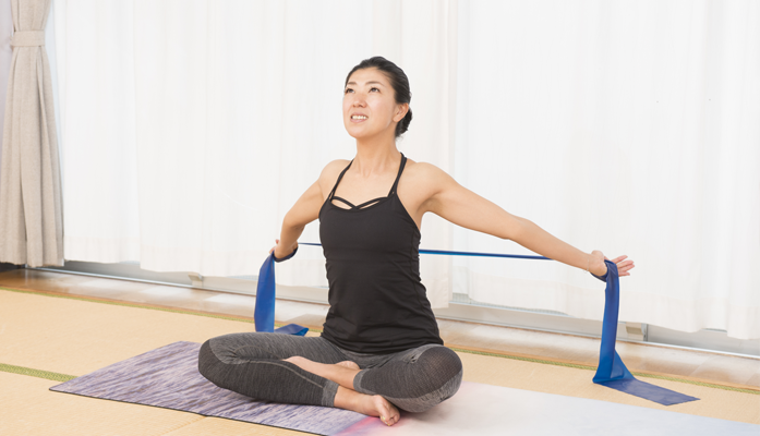 Lady using blue band to for yoga